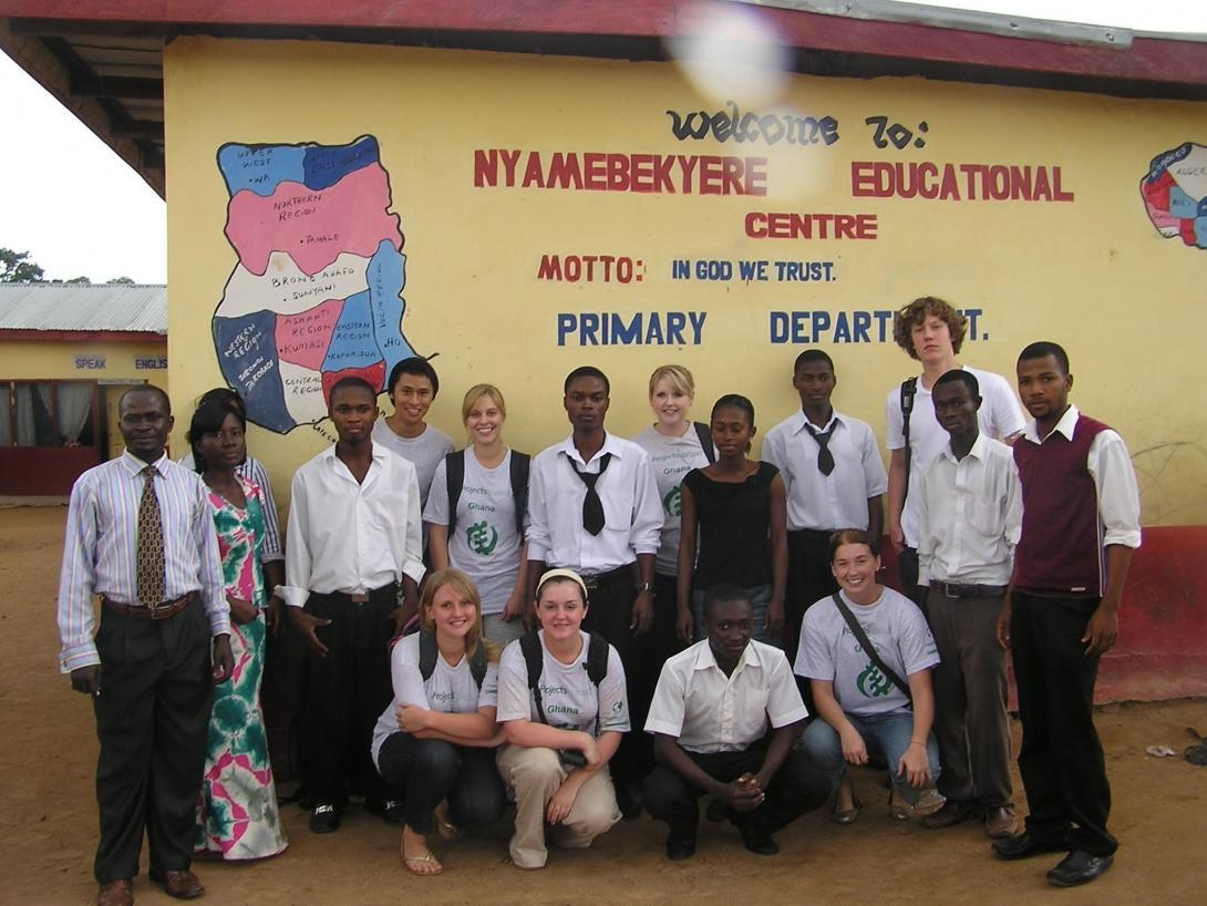 Projects Abroad volunteers and their students outside their volunteer IT teaching placement in Ghana.